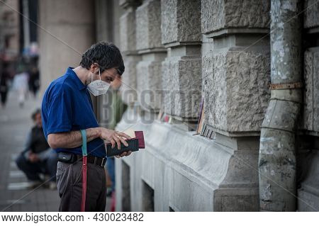 Belgrade, Serbia - May 24, 2021: Male Client Reading A Book In Front Of A Bookstore Wearing A Respir