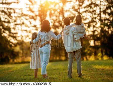 Happy family at sunset. Father, mother and children are running, having fun and enjoying summer evening.