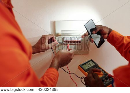 Hands Of Technicians Using Multimeter When Testing Electric Current In Watt Hour Meter