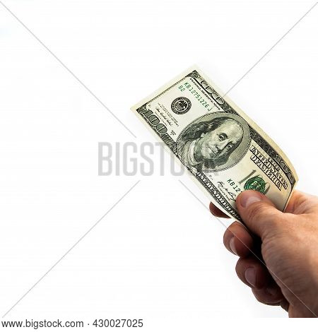 A Hundred-dollar Bill In His Hand On A White Background. Isolated. One Hundred American Dollars Bill