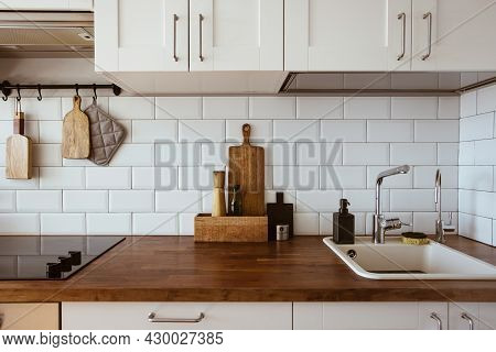 Kitchen Brass Utensils, Chef Accessories. Hanging Kitchen With White Tiles Wall And Wood Tabletop.ki