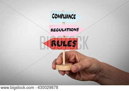 Compliance, Regulations And Rules Concept. Arrow Pointing Signs In A Womans Hand