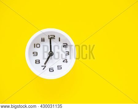 Top View, Flat Lay, White Clock Show Time At 7 O'clock On Office Yellow Workplace Tabletop. Copy Spa