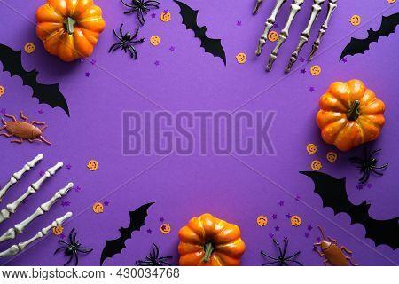 Happy Halloween Holiday Concept. Halloween Decorations, Skeleton Hands, Bats, Pumpkins On Purple Bac