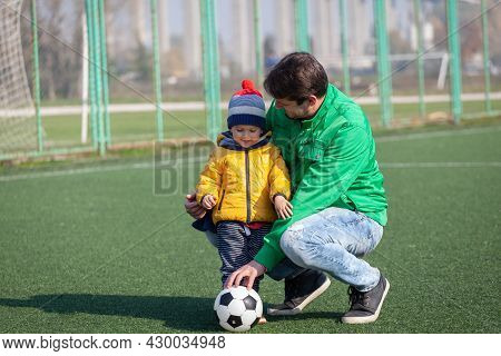 Father With His Little Son Having Fun, Playing Football, Soccer In The Park