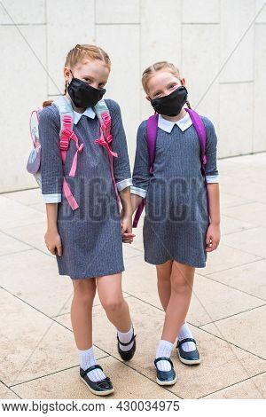Two Elementary School Students In Medical Masks On The Face. Sisters With School Bags. Back To Schoo
