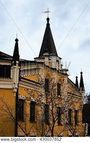 Picturesque Vintage Building With Roof Spiers. Yellow Brick Wall With Decoration. Spring Morning Lan
