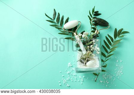 Skin Care Concept With Face Rollers On Mint Background
