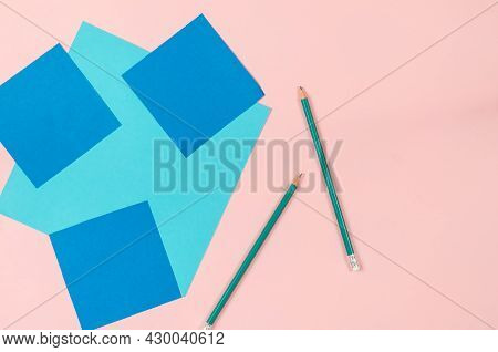 Sheets Of Colored Paper And Green Pencils On A Pink Background. Square Blue And Light Blue Sheets. T
