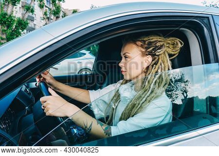 Woman With Dreadlocks Driving A Car. Profile.