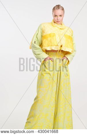 Full length portrait of a stylish girl posing at studio in fashionable summer clothes. White background. Fashion shot. Bright summer style.