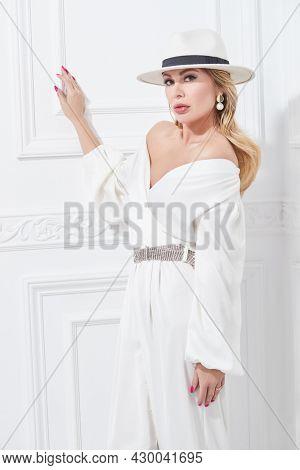 A wealthy middle-aged woman in a chic white suit, elegant hat and jewelry poses in a classic white interior. Luxury lifestyle. Beauty, fashion.
