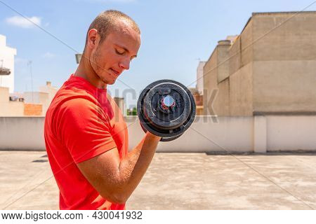 Horizontal Shot Of Handsome Muscular Man Lifts Dumbbell Outdoor, Gets Ready For Weight Lifting Train