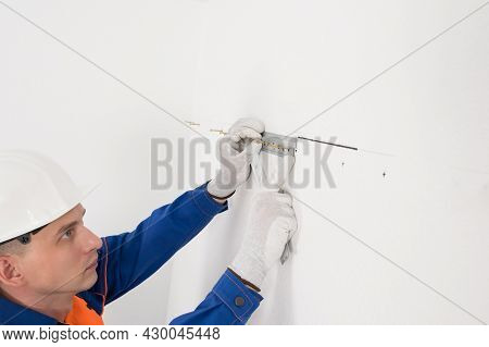 The Worker Attaches To The White Wall The Fasteners For Hanging The Cabinets Of The Kitchen Furnitur