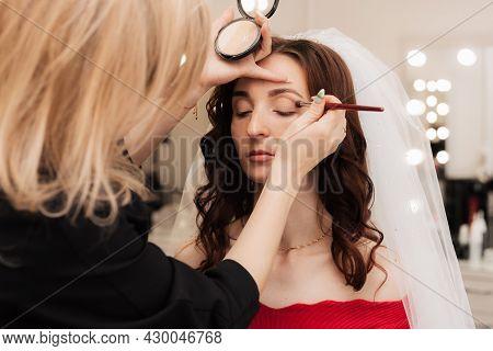 Girl Makeup Artist Brush To Apply Eye Shadow On The Eyelid Of The Model.
