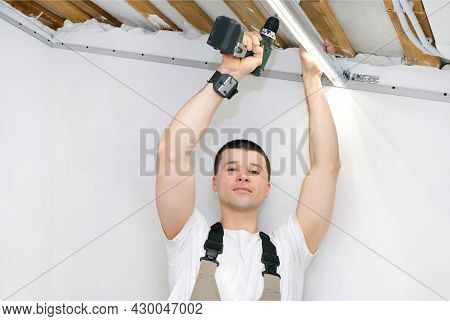 Man Makes Home Repairs. Preparing To Install A Stretch Ceiling. Installation Of Luminaires