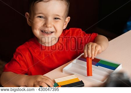 Child Boy Sculpts Figures From Multi-colored Plasticine Sitting At A Table. Preschool Education. Hob