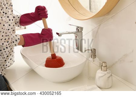 Woman Using Plunger To Unclog Sink Drain In Bathroom, Closeup