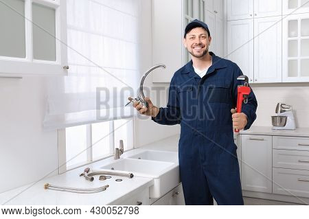 Professional Plumber With Water Tap And Wrench In Kitchen
