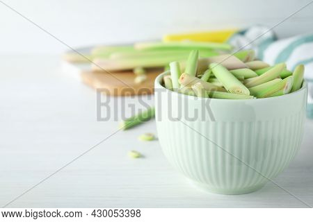 Bowl With Fresh Lemongrass Stalks On White Table, Closeup. Space For Text