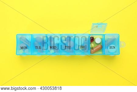 Pill Box With Medicaments On Yellow Background, Top View