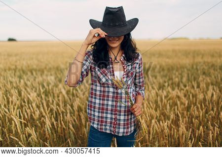 Woman American Farmer With Sheaf Wheat Ears Wearing Cowboy Hat, Plaid Shirt And Jeans At Wheat Field