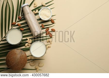 Different Vegan Milks And Ingredients On Beige Background, Flat Lay. Space For Text