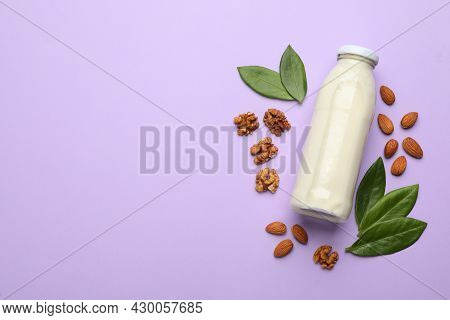 Bottle Of Vegan Milk, Walnuts And Almonds On Violet Background, Flat Lay. Space For Text