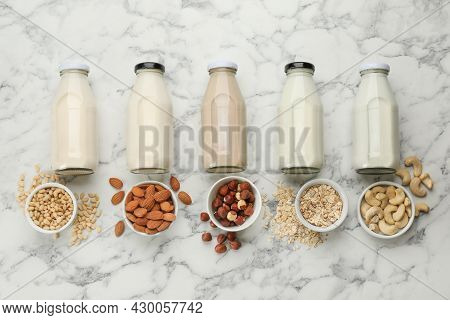 Different Vegan Milks And Ingredients On White Marble Table, Flat Lay