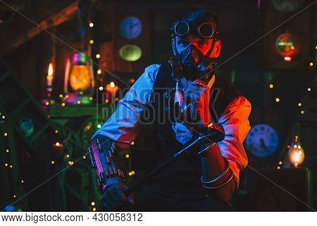Cyberpunk Post-apocalypse Cosplay. A Male Engineer In Glasses And A Gas Mask In A Workshop