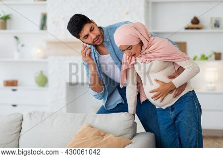 Pregnant Muslim Woman Having Prenatal Contractions, Caring Husband Calling Doctor On Smartphone, Fre