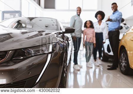 Happy Young Salesman Helping African American Family Choose Luxury Car At Vehicle Dealership, Select