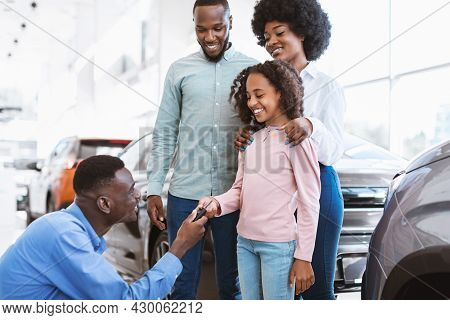 Happy Black Family Buying New Car, Salesman Giving Them Key At Auto Dealership