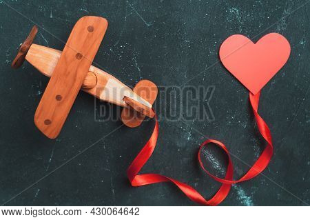 Wooden Toy Airplane Biplane On A Dark Background With A Red Ribbon And A Heart.