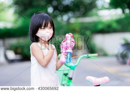 Happy Child Playing Bubble Gun At Outdoors With Green Bicycle. Kid Wearing Orang Cloth Face Mask Pre