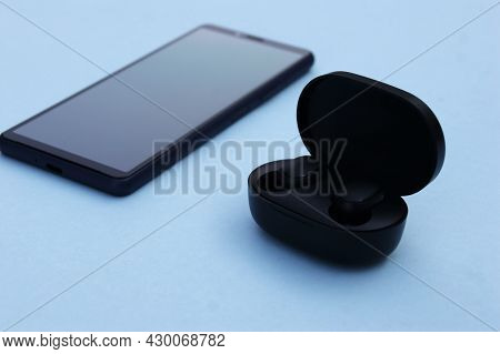 Smartphone And Wireless Headphones Or Earbuds With Charging Case On Bright Blue Background. Music Te