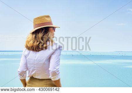 Rear View Shot Of Woman Looking At Sea View And Sailboats