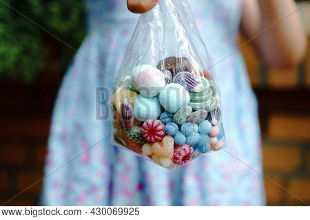 Close-up Of Preschool Girl With Bag With Candy Bonbons And Lollipop. Different Sweets In A Bag. No F