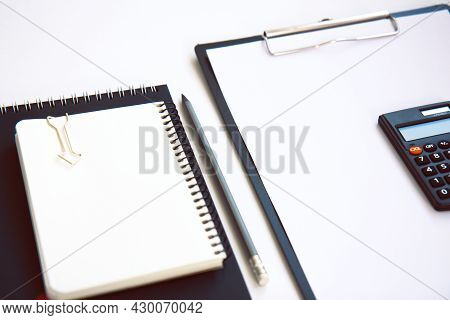 Black Clipboard With Blank Paper, Calculator And Notebook Isolated On White Background. Concept Of D
