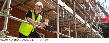 Panoramic web banner smiling male builder foreman, construction worker or architect on site wearing a white hard hat, holding a clipboard and drinking a mug of coffee or tea panorama header