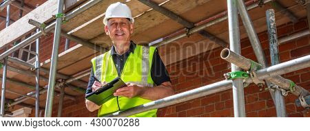 Panoramic web banner header male builder foreman, construction worker, contractor or architect on building site writing on black clipboard laughing, smiling and happy panorama