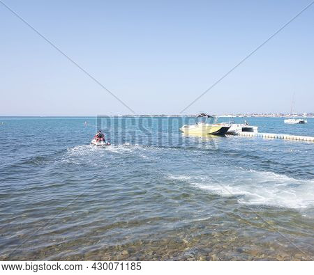 A Man On A Jet Ski Drives Off The Coast To Go For A Ride On The Sea. Rest And Spending Time At Sea.