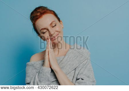 Happy Calm Redhead Grateful Woman Holding Hands In Prayer Gesture With Closed Eyes And Tilted Head,