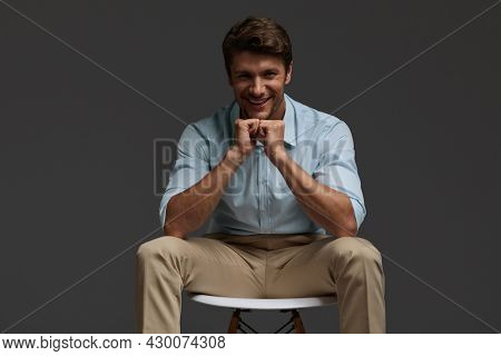 Young beautiful cheerful european businessman sitting on chair. Bearded man with dark hair wear shirt with trousers and looking at camera. Isolated on dark gray background. Studio shoot. Copy space
