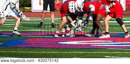 High School Lacrosse Players Are Fighting For Possession Of The Ball Trying To Scoop It Up During A
