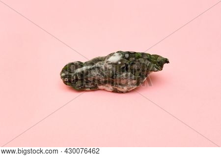 Spoiled Food. Organic Waste. The Cucumber Has Grown Moldy And Started To Rot. Pink Background.