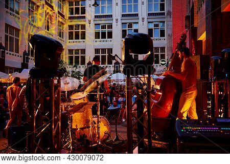 Musicians Perform In Front Of Spectator In Restaurant At Night In Wroclaw, Poland. Street Music. Wro