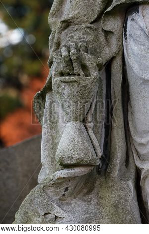 Hourglass In The Hand Of A Grim Reaper In A Cemetery