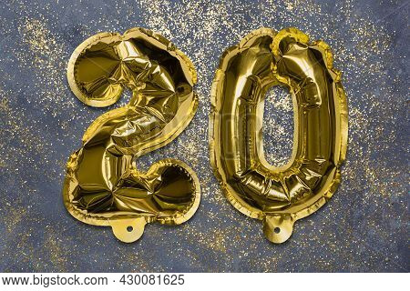 The Number Of The Balloon Made Of Golden Foil, The Number Twenty On A Gray Background With Sequins.