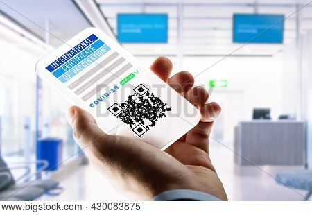 coronavirus, technology and health concept - close up of man's hand holding transparent smartphone with international certificate of covid-19 vaccination on screen over airport lounge background